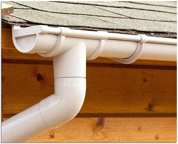 Пластиковый водосток с крыши деревянного дома фото